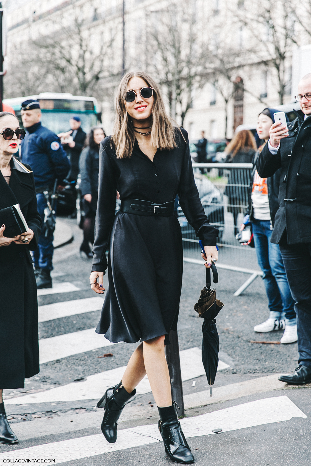This killer black on black outfit will guarantee you the attention of everyone you pass! Combining a belted shirt dress with patent leather ankle boots and authentic retro shades, this model has nailed the trend. Via Collagevintage. Brands not specified.