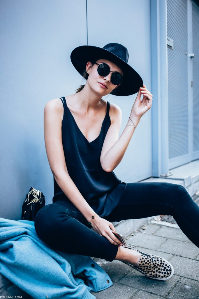 Paulien Riemis looks cool and casual in this all black outfit consisting of black jeans, a simple vest top, and an awesome retro style fedora. Choose to jazz up a simple all black style by wearing a pair of statement shoes like this leopard print pair which we love! Brands not specified.