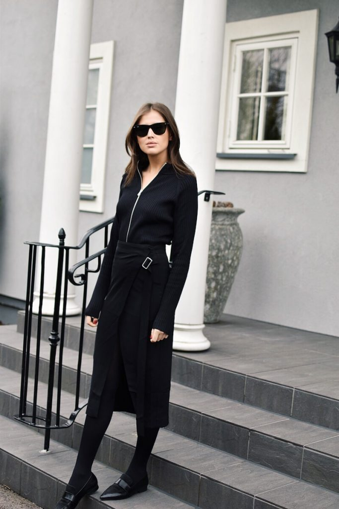 There is nothing sleeker than the black on black aesthetic. Darja Barannik wears the look in a cute knitted zip up sweater paired with a super stylish wrap around skirt. A pair of shades finishes off the look, adding those cool girl vibes we all crave! Brands not specified.