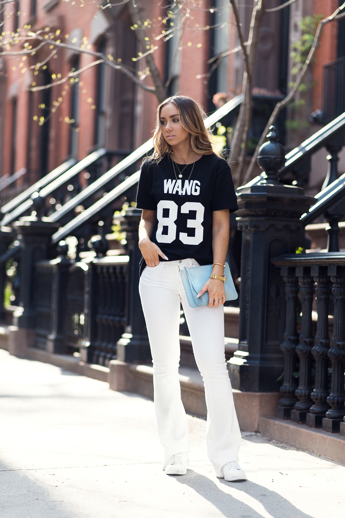 Lisa Olsson is wearing a white pair of denim bootleg jeans and a baby blue clutch bag from Gina Tricot with a black graphic tee