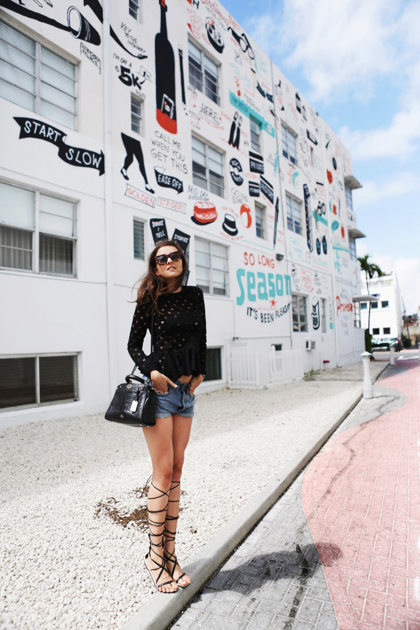Andy Torres is wearing a black top from Stine Goya, denim shorts from MiH, sandals from Zara, bag from Coach and the sunglasses are from Celine