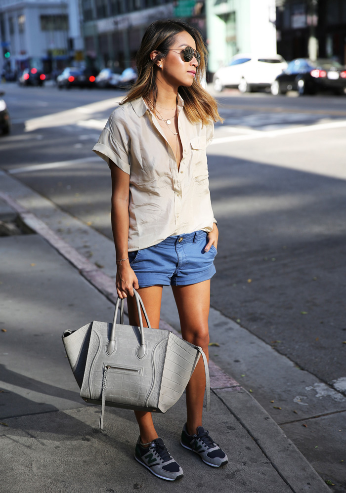 Julie Sarinana is wearing a khaki silk shirt from Everlane, midi shorts from American Eagle and the sneakers are New Balance 420