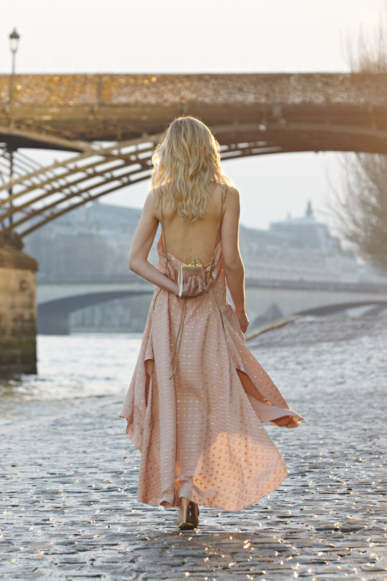 Clémence Poésy is wearing a beige pink low back sleeveless dress and bag from Chloe