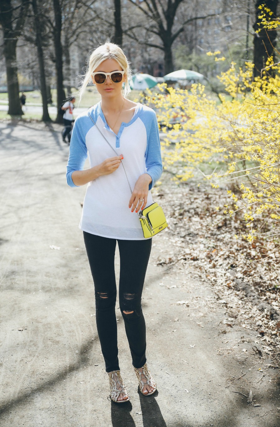 Amber Fillerup Clark is wearing a blue and white baseball T-shirt from Free Press, black jeans from Rag & Bone, sunglasses from Wildfox, yellow mini bag from Milly and the sandals are from Joie