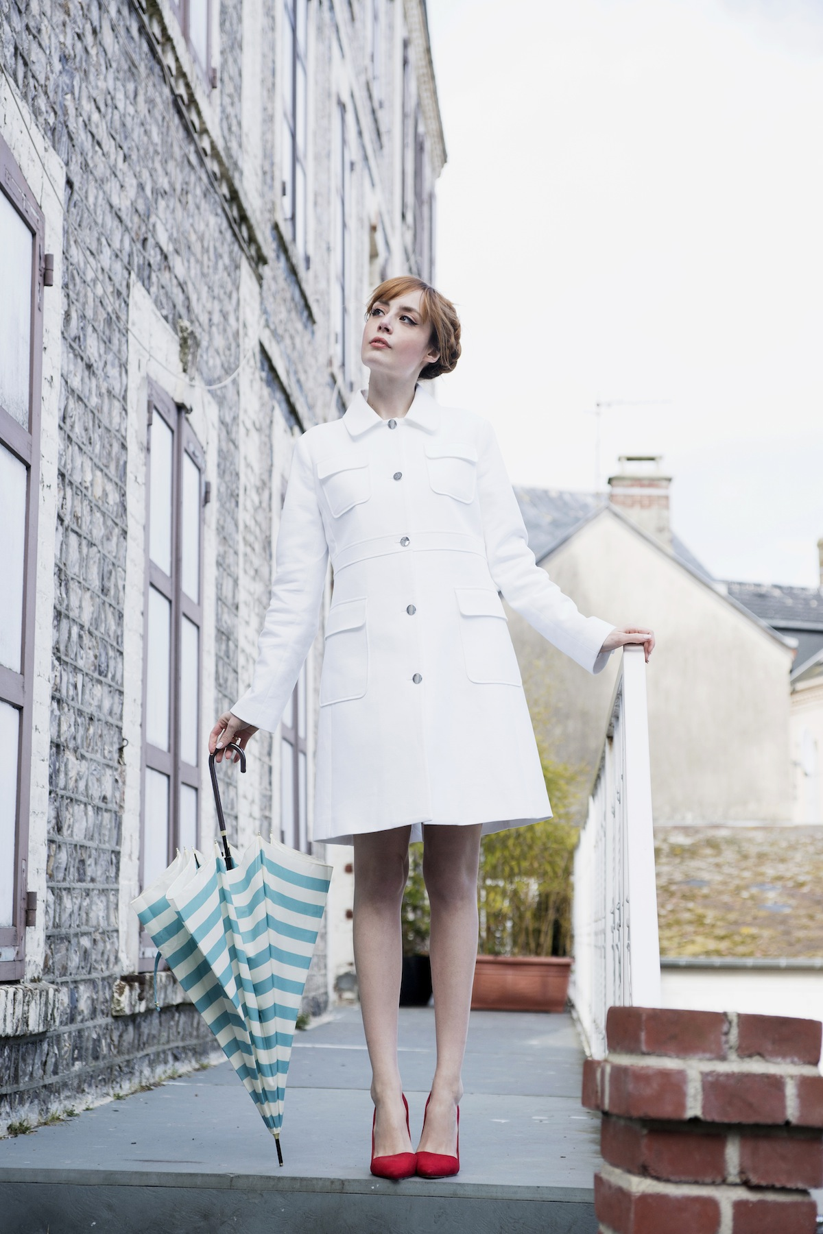 Louise Ebel is wearing a white coat from Paul & Joe and the red shoes are from Alice + Olivia