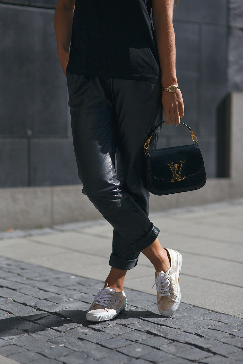 Via Just The Design: Johanna Olsson is wearing a pair of black leather Designers Remix pants with a Zara top, a Louis Vuitton clutch bag and Suprega pumps