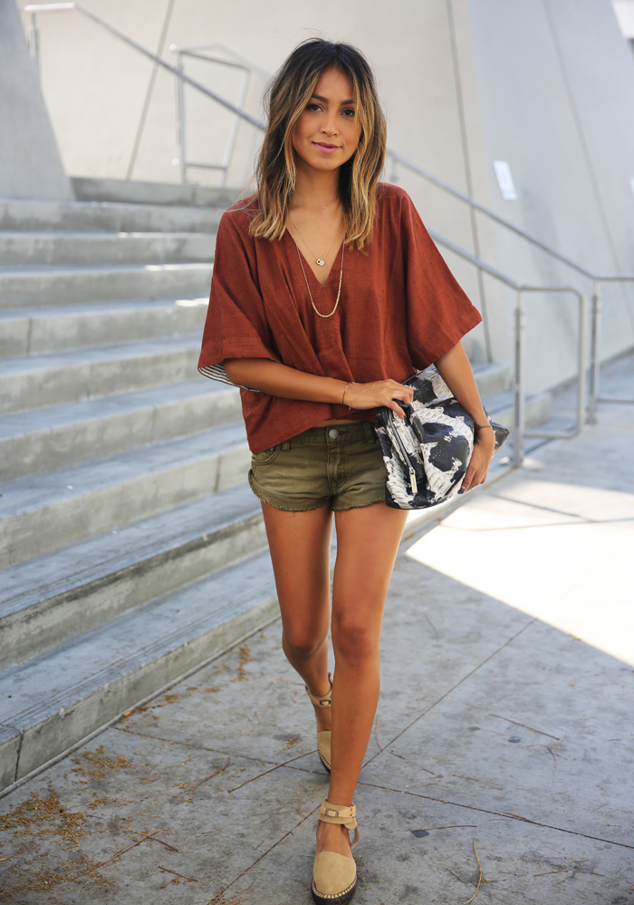 Street Style 2015: Julie Sarinana is wearing a cropped v-neck top with khaki green shorts and beige sandals all from Free People