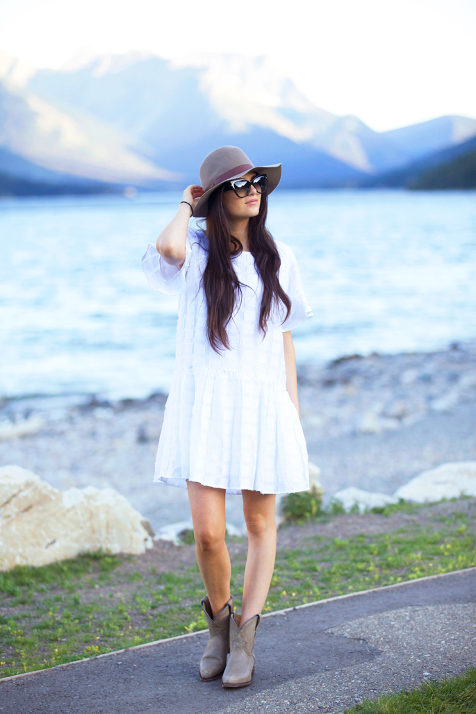 Rachel Parcell is rocking an ultra cool, ultra feminine summer style here; combining a beautiful floaty white dress with a pair of suede cowgirl boots and a matching wide brimmed hat. Dress: Anthropologie, Boots: Frye, Hat: Calypso St. Barth.