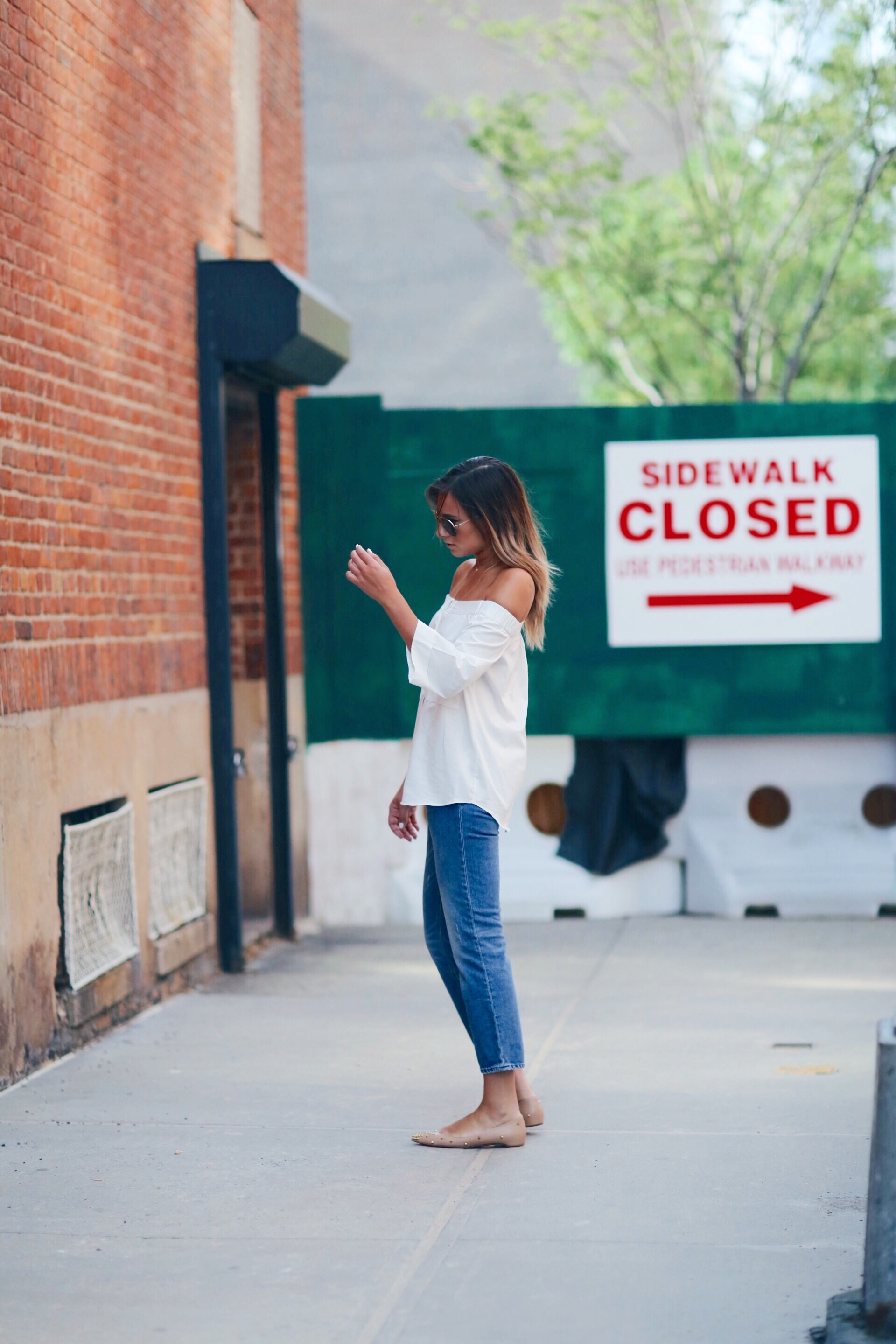 Danielle Bernstein is looking timelessly classic in blue jeans and a white off the shoulder shirt! Top: H&M, Jeans: ACNE, Flats: Christian Louboutin