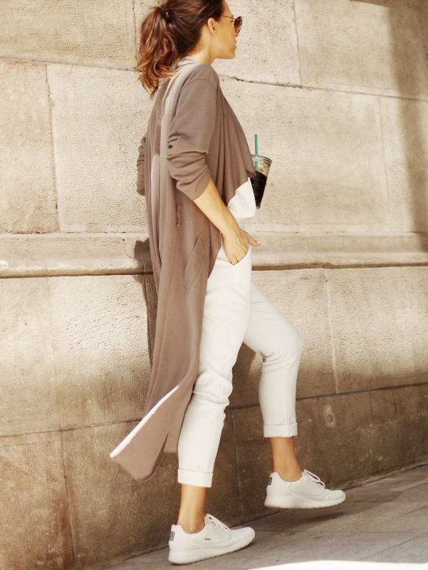 A brown draped trench coat, white jeans and sneakers is a great look going from Summer to Fall. Via Audrey Leighton Rogers