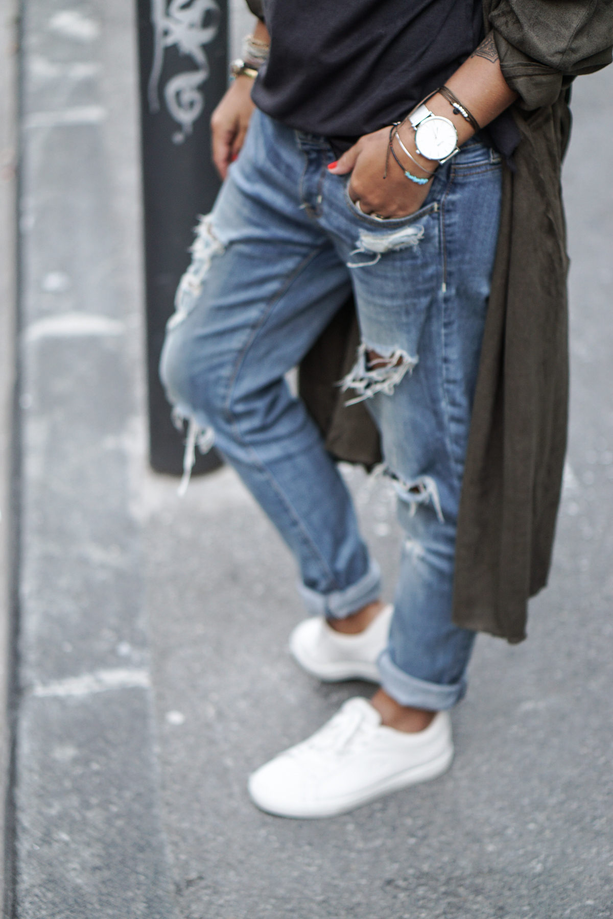 Camille Callen wears distressed denim jeans with white sneakers and trench jacket. Top: Zara, Trench: Avah, Jeans: American Eagle.