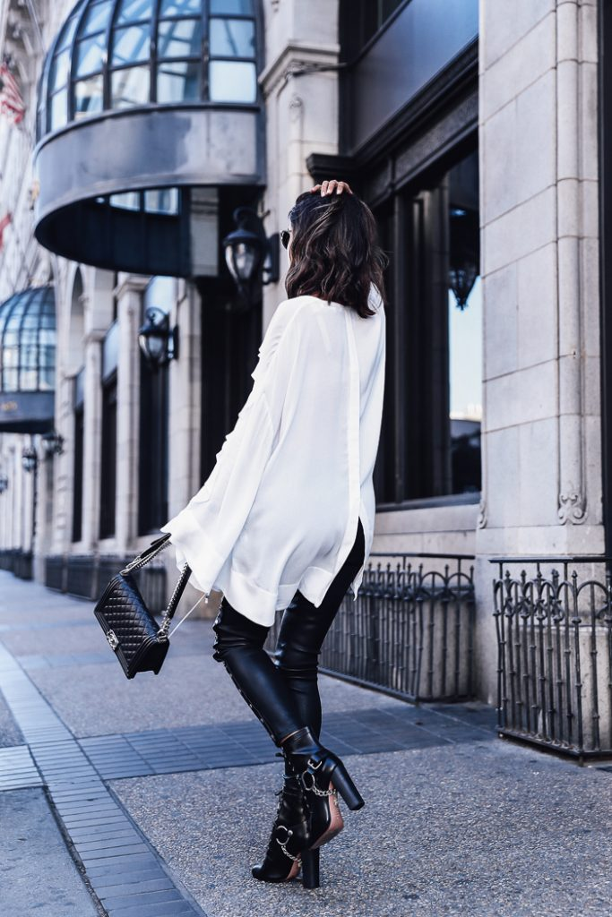 Annabelle Fleur creates a classic rocker chick style here, wearing an oversized sheer white shirt with leather leggings and spiked boots! We adore this monochrome look and suggest you give it a try.   Trousers: IRO, Top: Birlie, Boots: Aquazzura, Bag: Chanel.