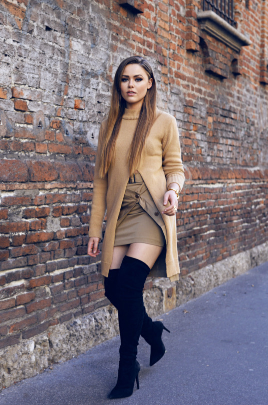 Kristina Bazan wears black over the knee boots with a tan slit-detailed pullover and matching skirt. Top/Skirt: Storets, Boots: Stuart Weizman.