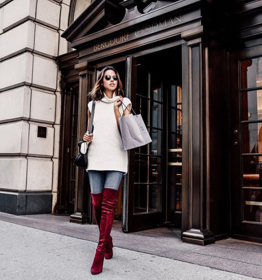 Annabelle Fleur makes a statement in these crimson over the knee boots, jeans, and a knitted vest. Boots: Stuart Weitzman.