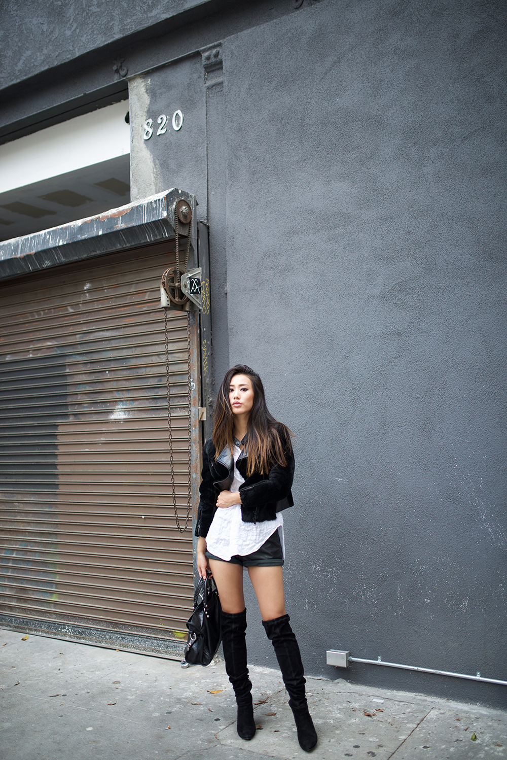 Jenny Ong wears leather mini shorts with black over the knee boots. Jacket: Phillip Lim, Top: Lou & Grey top, Shorts: JBrand, Boots: Ted & Muffy, Bag: Balenciaga.