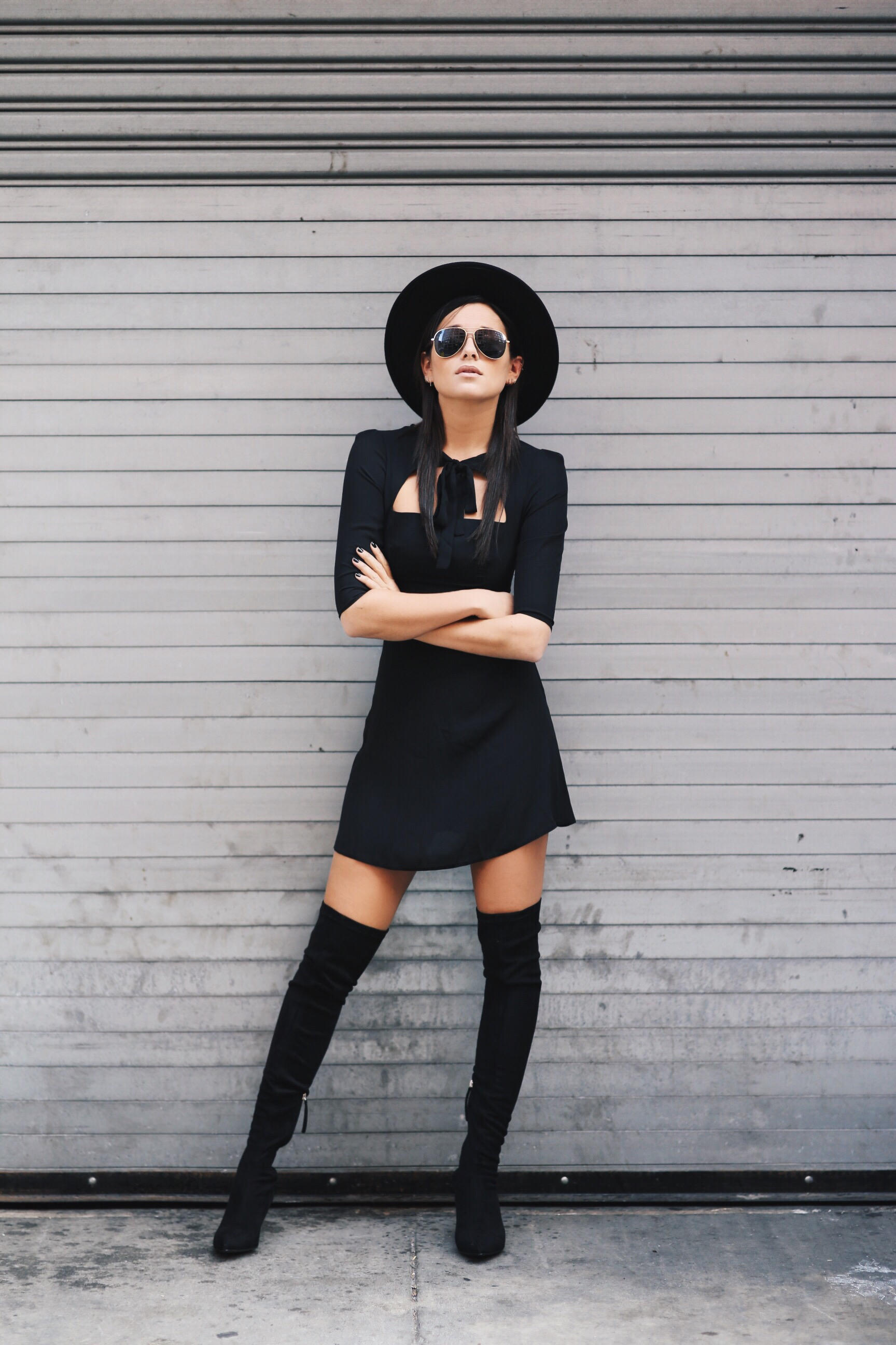 Danielle Bernstein keeps it sleek and simple, wearing a black mini dress and hat with black over the knee boots. Dress: LOVE, Boots: Zara.