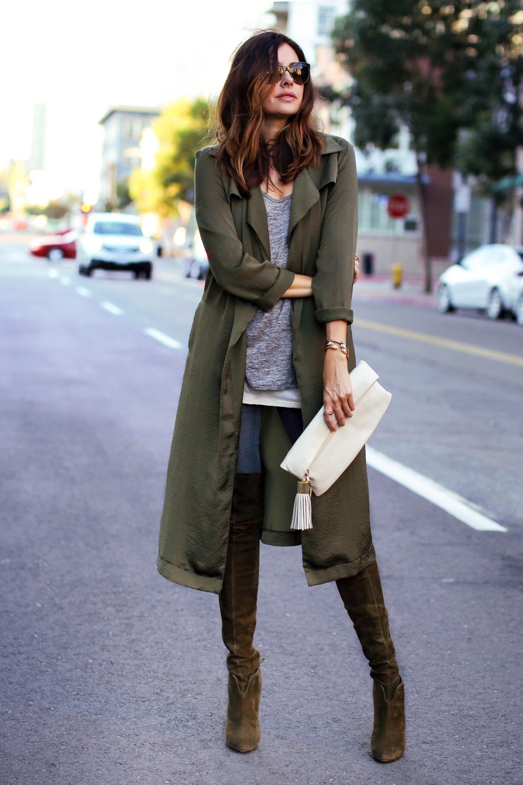 A long flowing trench coat can be perfectly accesorised with a casual tee and over the knee boots. Via Erica Hoida. Trench: Girls on Film, Shirts: Rag & Bone and David Lerner, Jeans: Asos, Boots: Aquazzura, Clutch: India Hicks, Bracelets: Vita Fede.