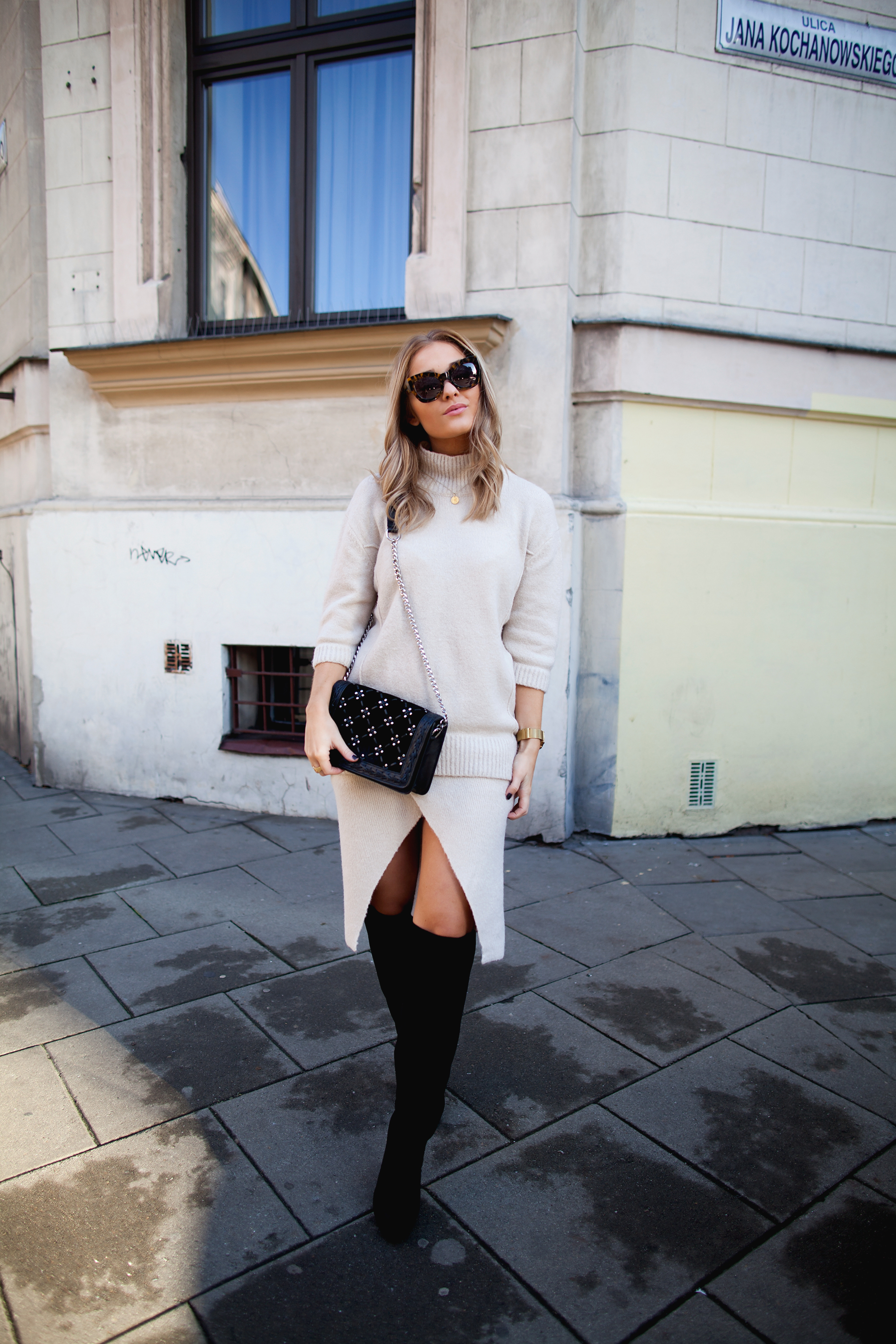 Over the knee boots are the perfect addition to a slitted skirt and pale sweater outfit, as worn here by Marie Wolla. Wear your pair with a similar skirt to recreate this funky look. Knit Set: Gina Tricot, Bag: Zara, Boots: Nelly.