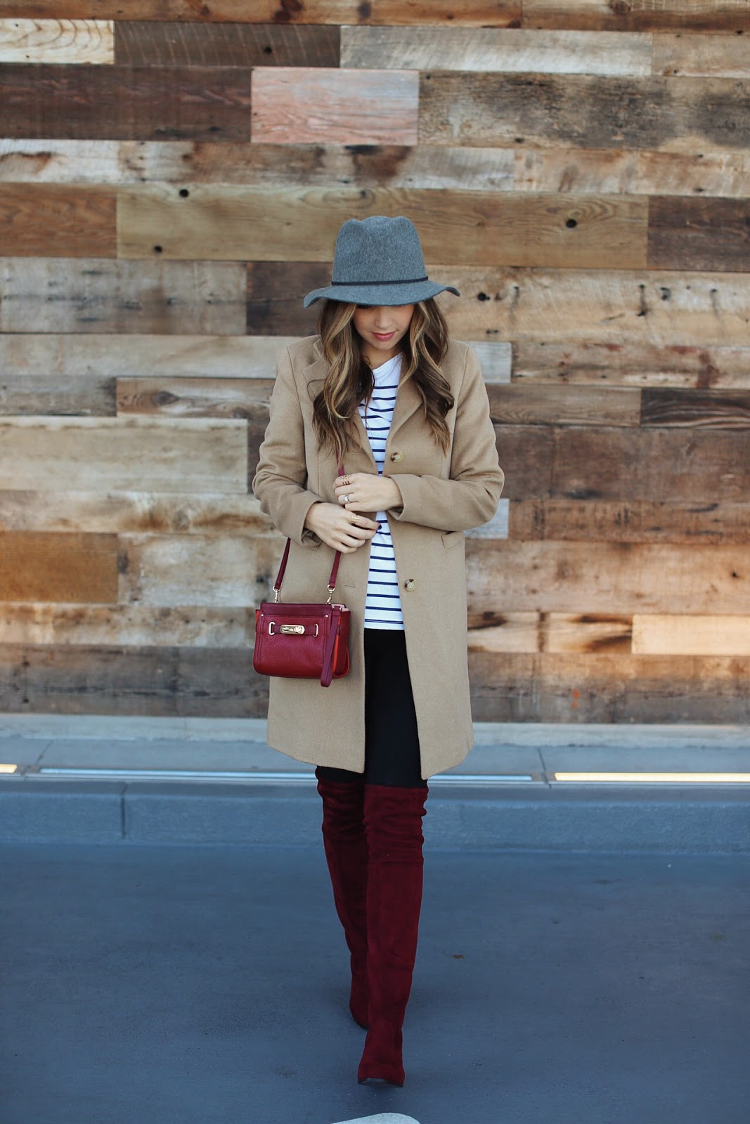 Over the knee boots will look fantastic with a classic camel coat. Merrick demos a pair of red velvet over the knee boots; the perfect tone to match the rest of the look. Coat/Hat: Zappos, Boots: Choies, Shirt: Asos, Bag: Coach.
