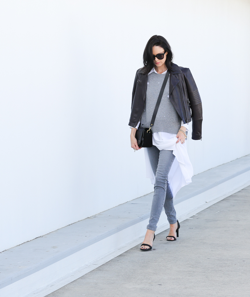 Fiona Edwards wears a pair of grey skinny jeans with a stylish cropped leather jacket. Top: Equipment, Knit: Enza Costa, Jeans & Jacket: J Brand, Shoes: Rag & Bone.