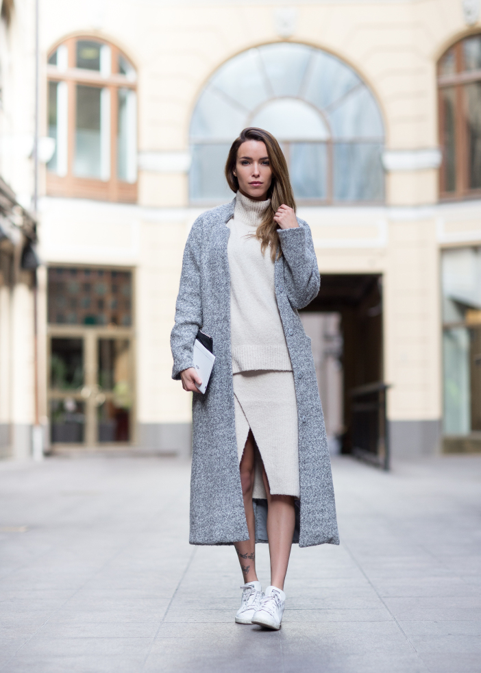 Julia Toivoloa wears a gorgeous pastel maxi coat over a cream knit sweater and slit-detailed skirt. Sweater/Skirt/Coat: GinaTricot, Scarf: Acne, Shoes: Adidas.
