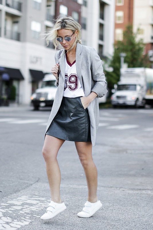 Mary Seng wears a leather mini skirt with a smart grey overcoat and casual white sneakers. Jacket: McGinn, Top: Anine Bing, Skirt/Sneakers: Zara.