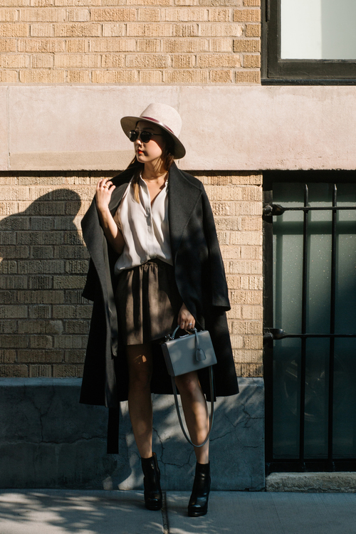 Erica Choi looks cool and casual in this ovesized black coat. Pair with a cute box bag to complete the look. Coat: Kuho, Shirt: Everlane, Skirt: Aritzia, Shoes: Chanel, Hat: Janessa Leone.