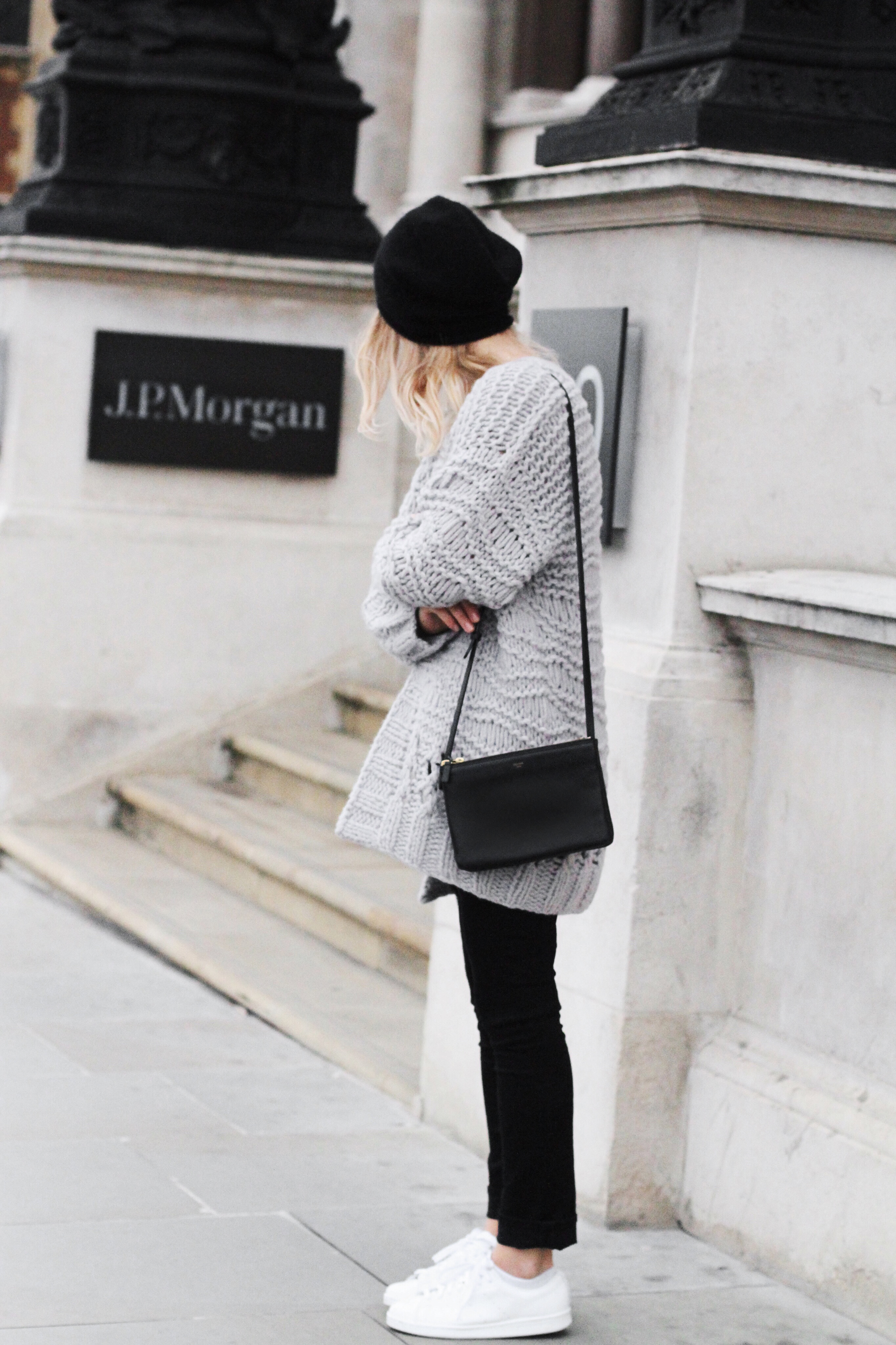 Black jeans and white sneakers will always make the perfect combination. Mirjam Flatau wears this look with an oversized knit sweater and a cute black beanie. Cardigan: Ira Von Arnim, Jeans: AYR, Tee: Bassike, Bag: Celine, Beanie: Cos.