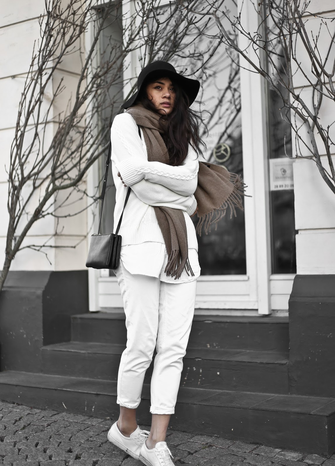Monja Wormser is a picture in white, combining simple sneakers with white combat trousers and a cable knit sweater. Breaking up the whitewash is a gorgeous cotton scarf and a stylish vintage fedora. Sweater/Shirt: Magasin Du Nord, Jeans: Topshop, Sneakers: Axel Arigato.