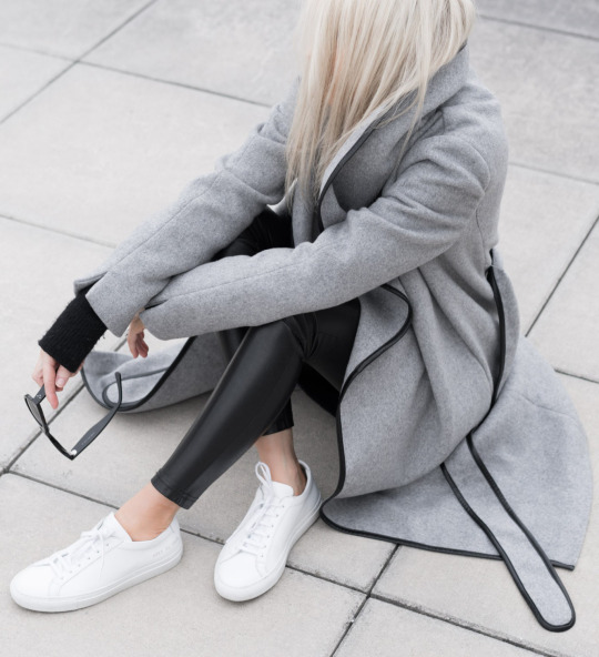 Figtny is rocking leather leggings as a fashionable alternative to jeans here, pairing them with a cute winter look consisting of simple white sneakers and a stylish grey trimmed maxi coat. Outfit: Decjuba.