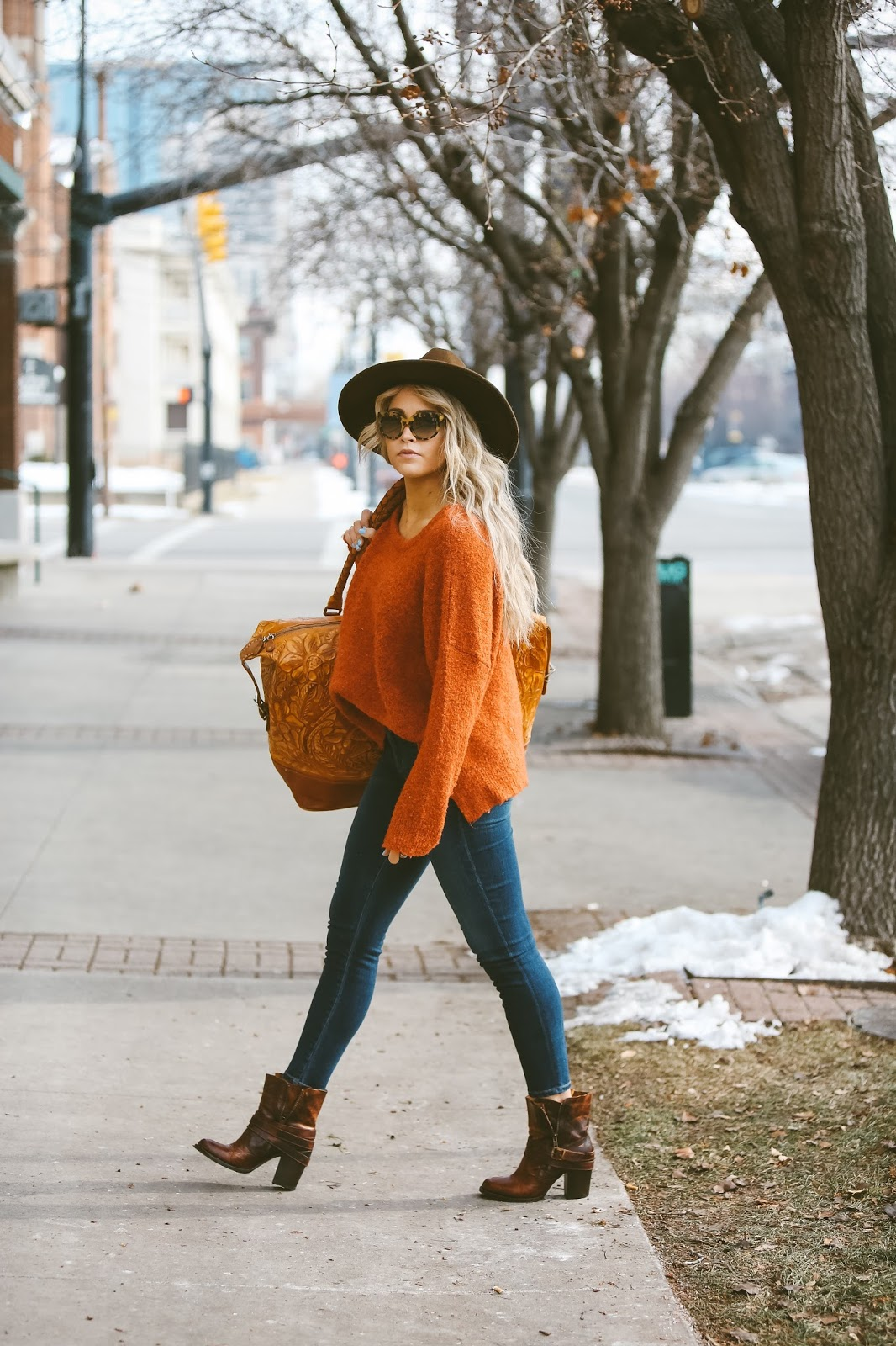 Wear a bright statement knitwear piece such as this orange sweater with casual denim jeans to get the stylish winter vibes rocked here by Cara Loren Van Brocklin. Add a wide brimmed fedora if you want that classic retro feel. Sweater: Nordstrom, Jeans: ShopBop, Shoes: Steve Madden.