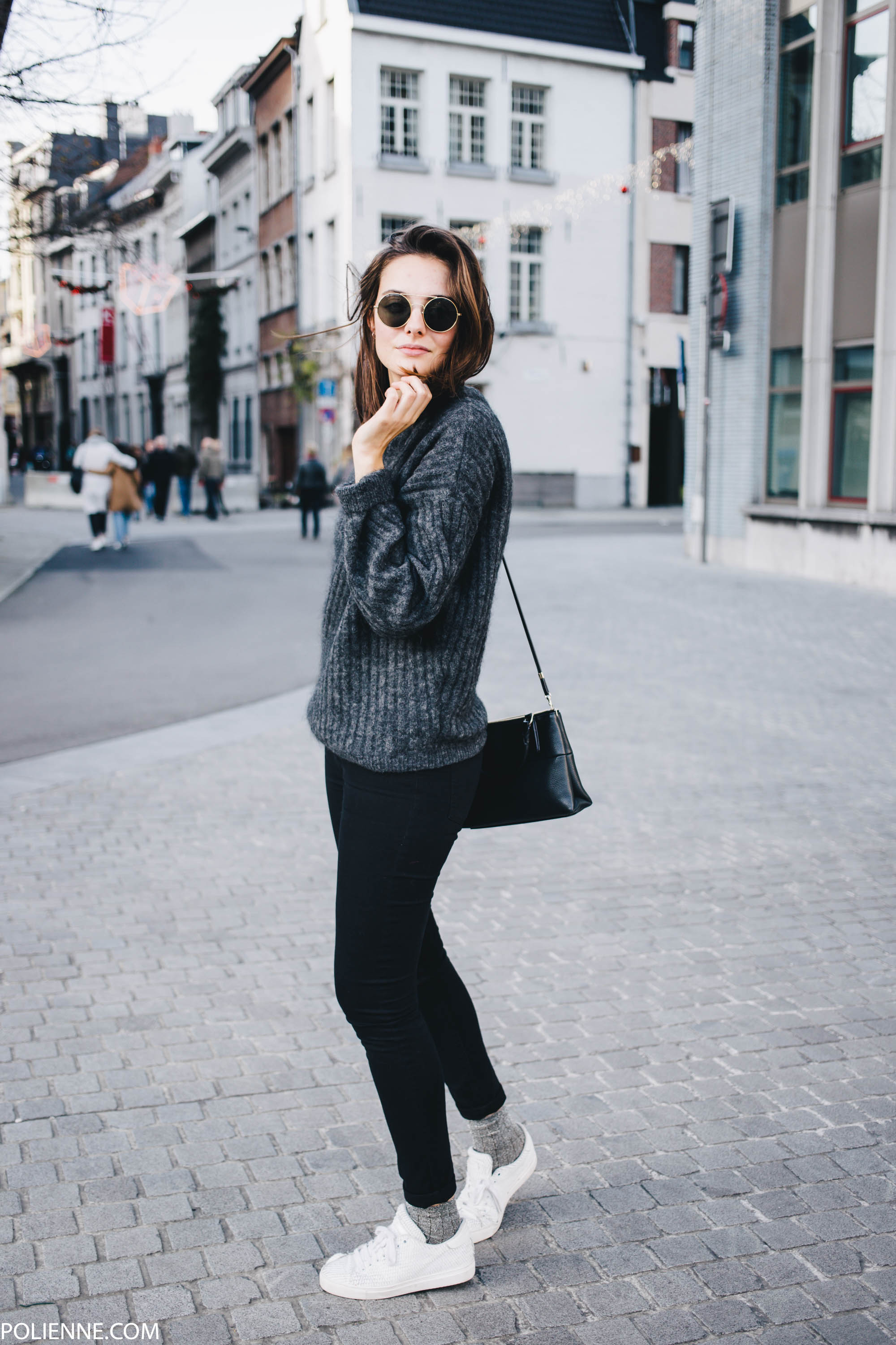 A simple grey knitted sweater worn with a pair of cute matching socks, white sneakers, and black denim jeans makes for a simplistic but stylish winter look. Via Rosanna van Billie-Rose. Jacket: H&M, Sweater: Acne, Denim: Cheap Monday, Sneakers: Pinko, Bag: Coach.