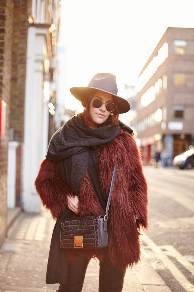 Dare to wear tinted faux fur this winter for an awesome festive look. Amy Spencer pairs this crimson coat with a cross body snakeskin bag and a vintage style fedora, creating an individual and unique aesthetic. Jacket/Hat: River Island, Scarf: Hush, Trousers: H&M, Bag: Jaeger, Boots: Senso.