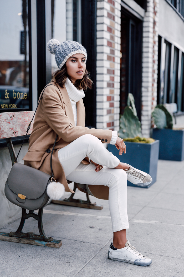 Annabelle Fleur breaks up an all-white outfit with a trendy camel coat and an adorable bobble hat from Urban Outfitters; creating an easy, cosy winter look. Trousers: AG Stevie Turtleneck Sweater: Joie Kajetan, Coat: Banana Republic, Hat: Urban Outfitters, Sneakers: Golden Goose.