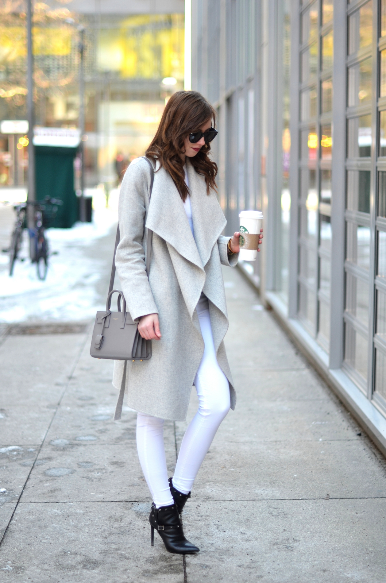 Barbora Ondrackova looks ultra sleek in this white jeans outfit consisting of a pale beige wrap coat and heeled ankle boots. These pieces make a winning combination which is perfect for a simple winter look! Top: Acne, Jeans: Mango, Coat: Zara, Bag: Saint Laurent, Boots: Valentino.