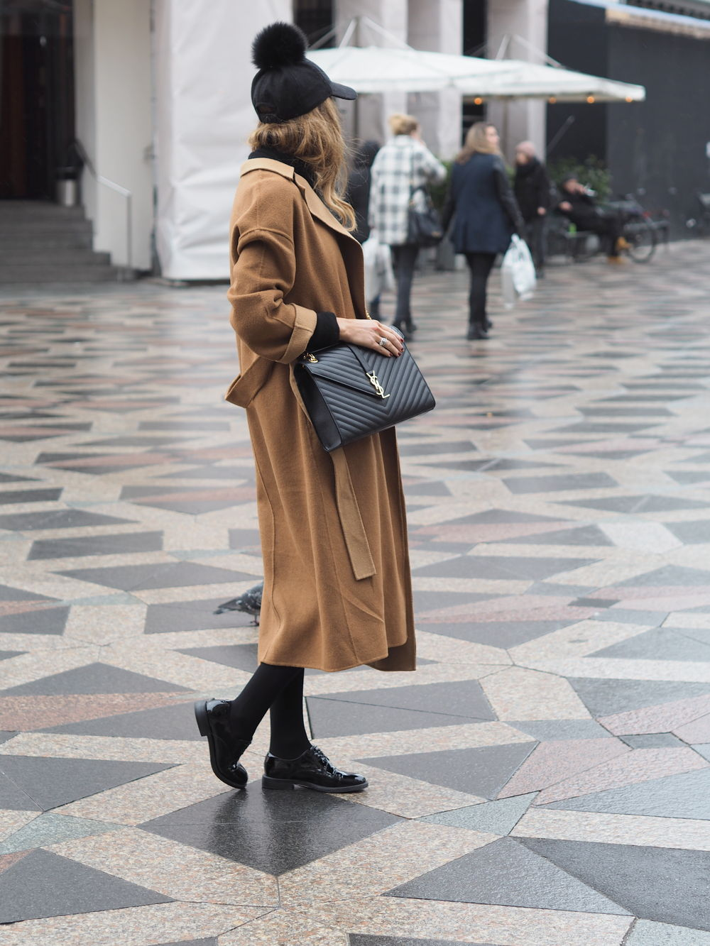 Benedichte is rocking the camel trend here, wearing this maxi coat with tights and patent black brogues for a classic, sophisticated winter look. A fluffy peaked cap will also add a cutesy edge to your outfit, as seen here. Coat: Zara, Cap: Twist & Tango, Shoes: Saint Laurent.