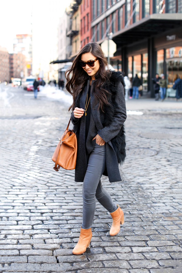 Kat Tanita is absolutely rocking the faux fur trend as a part of this cute winter outfit consisting of grey jeans, tanned leather boots, a smart grey coat, and a gorgeous fluffy gilet. Coat: Harris Wharf London, Jeans: Elliott, Vest: Max Studio, Bag: Meli Melo, Boots: Rag & Bone.