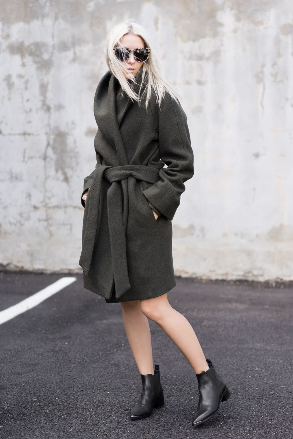 Figtny keeps it cool and sophisticated in this grey wrap coat from Artizia, worn with simplistic Chelsea boots and a pair of stylish shades. We like this for a smarter winter look, perfect for work or leisure. Coat/Knit/Scarf: Aritzia, Boots: Acne Studios.