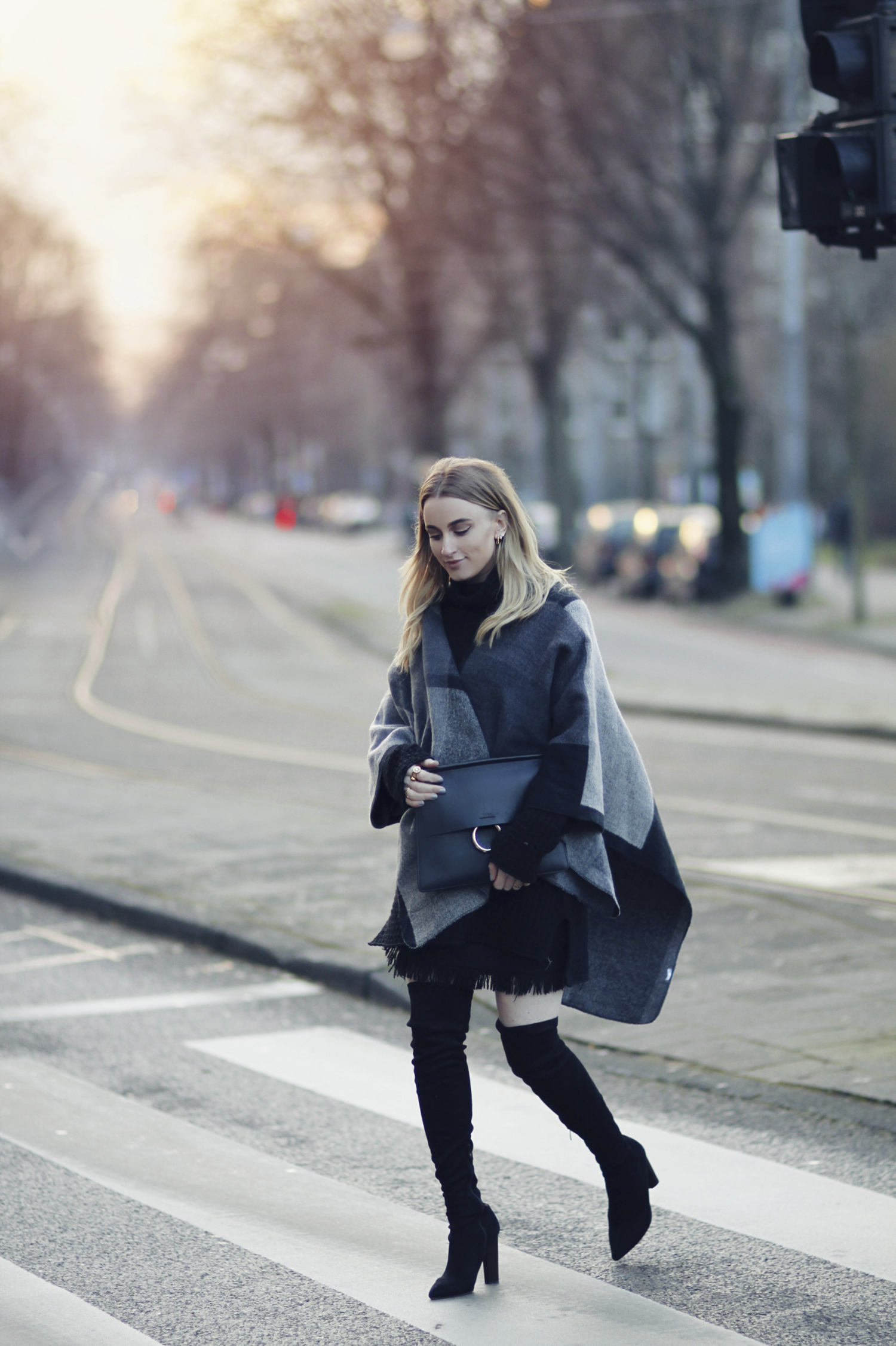 Noor De Groot is wearing thigh high boots with the poncho coat trend, in a stylish and authentic greyscale poncho which affords her an alternative and eye catching style! Boots: Public Desire, Skirt: Zara, Sweater: Baum und Pferdgarten, Poncho: Boohoo, Bag: Chloe.