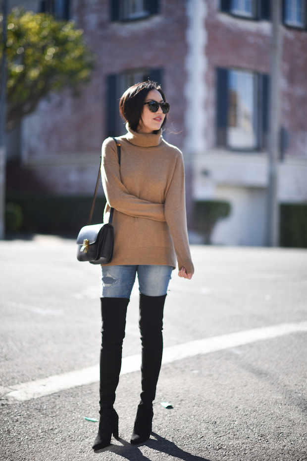 Ann Taylor is making a statement in these striking thigh high boots, worn with classic denim jeans and a beige rollneck sweater. An outfit such as this expresses cool and casual vibes; perfect for a cute winter style. Boots: Stuart Weitzman, Jeans: Madewell, Turtleneck: Everlane, Bag: Celine.