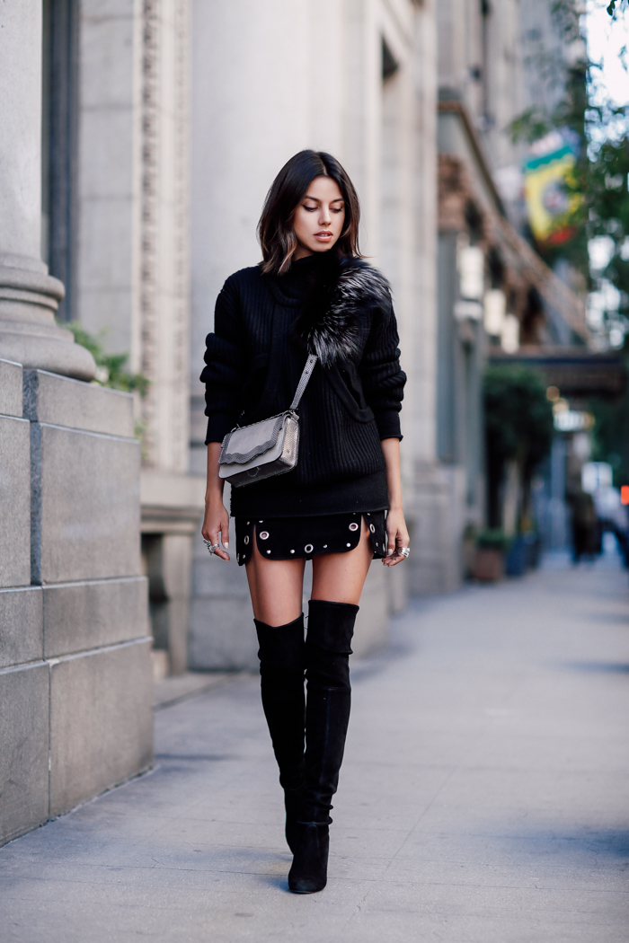 Annabelle Fleur is wearing thigh high boots with an alternative and edgy mini skirt, a simple knit sweater, and a faux fur collar. This look is individualistic and authentic, a definite winner! Skirt: Topshop, Sweater: IRO Paris, Boots: Stuart Weitzman.