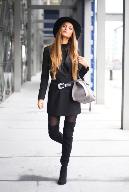A great way to wear thigh high boots is demonstrated here by Sandra Willer, who is wearing them with tights and a belted black rain mac, paired with a cute black fedora. Coat: Missguided.