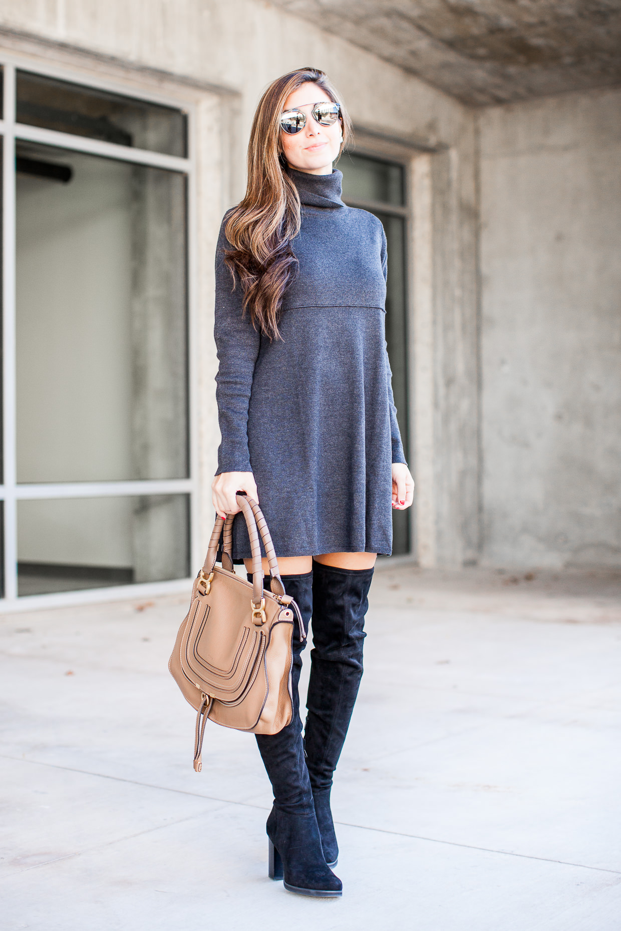 This is exactly how thigh high boots should be worn with dresses! Jessi rocks a simple and feminine sweater dress with a pair of leather boots and a beige handbag, creating an ultra cute overall style. Dress: Nordstrom, Bag: Chloe Marcie.