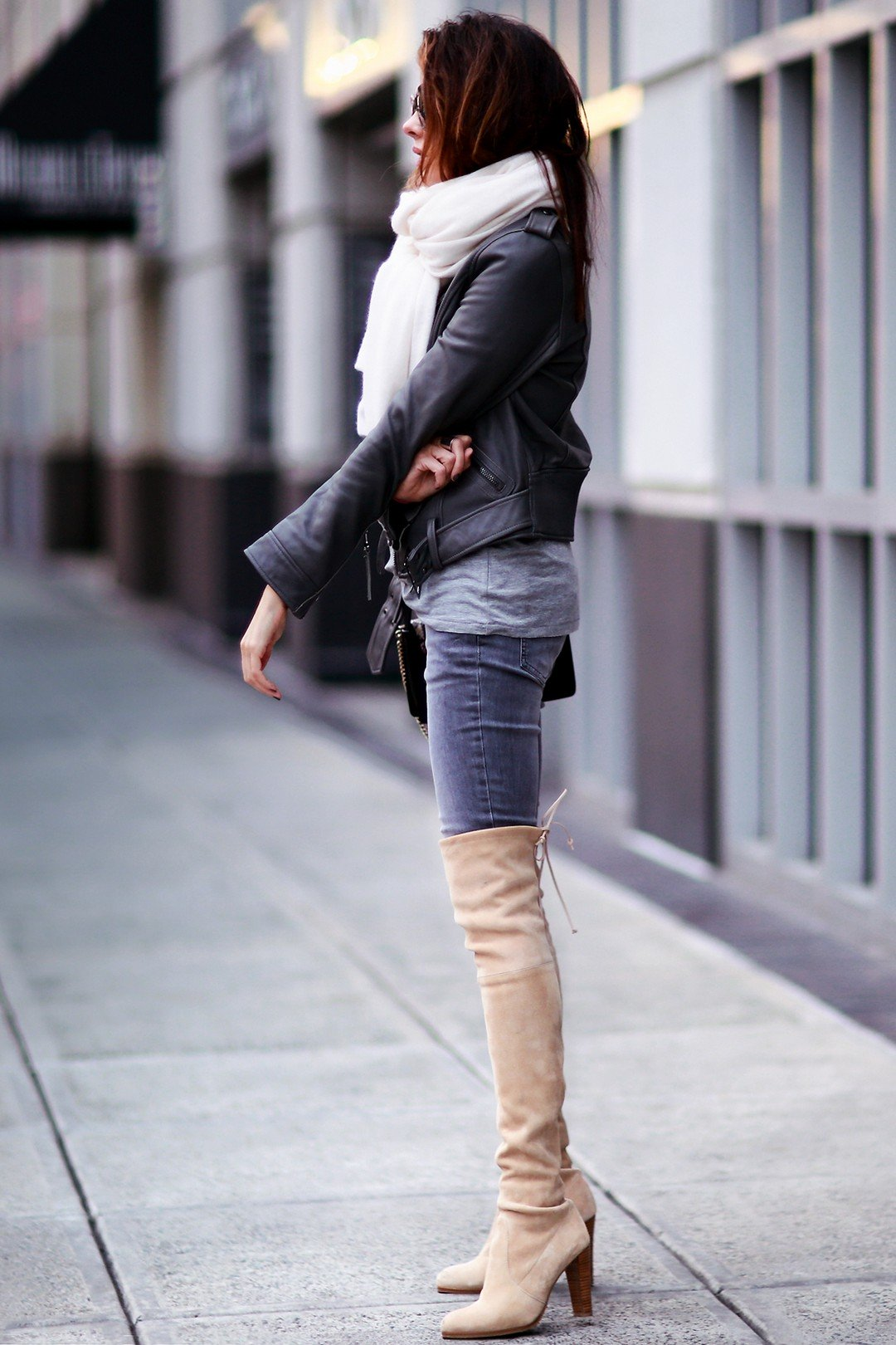 Erica Hoida demonstrates the versatility of thigh high boots, wearing a pair of pale blush coloured boots with denim jeans and a cropped leather jacket. Black is absolutely not the only appropriate colour; don't be afraid to try tinted boots! Jacket: Linea Pelle, Shirt: Tibi, Jeans: Aninie Bing, Shoes: Stuart Weitzman, Bag: Chloe, Scarf: White + Warren.