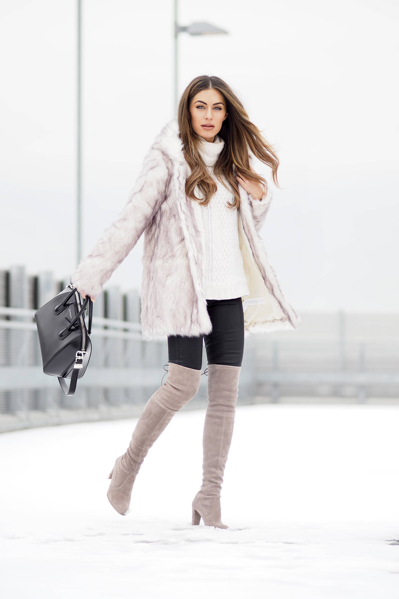 Coloured thigh high boots are always a winner! Lydia Lise Millen wears this gorgeous pastel pair with black jeans, a cream knit sweater, and a stunning faux fur coat from Boohoo. We love this look! Fur Coat: Boohoo, Jumper: Jigsaw, Bag: Givenchy, Jeans: Paige, Boots: Stuart Weitzman.