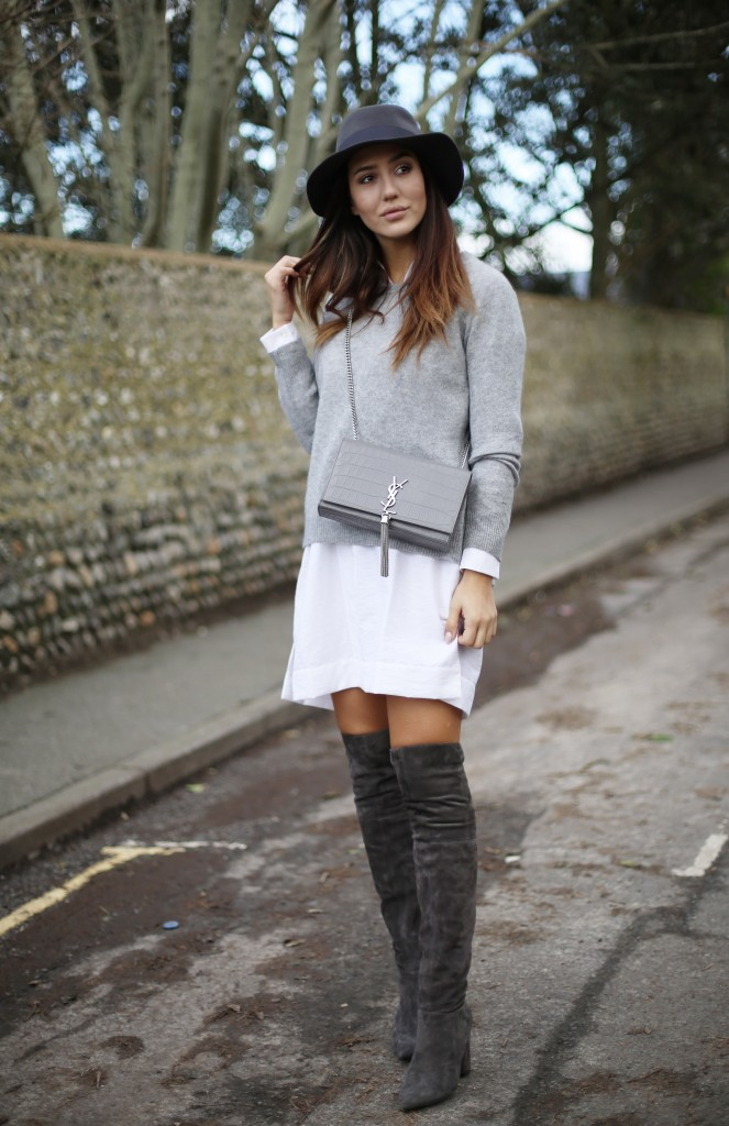 Tamara Kalinic débuts a cute and preppy style here, pairing marl grey thigh high boots with a white shirt dress and a thin grey sweater. Try adding a fedora to get the cool, casual vibes we see here. Shirt/Boots: Asos, Sweater: 360 Sweater, Hat: Maison Michel, Bag: YSL.