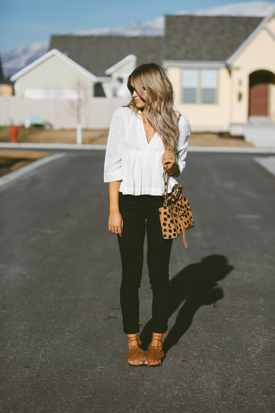Monochrome will simple never go out of trend! Cara Loren wears a contrasting black and white outfit consisting of a floaty v neck blouse and skinny black jeans. Wear this look with gladiator sandals to steal Cara's spring style. Top: Free People, Jeans: J Brand, Sandals: Steve Madden.