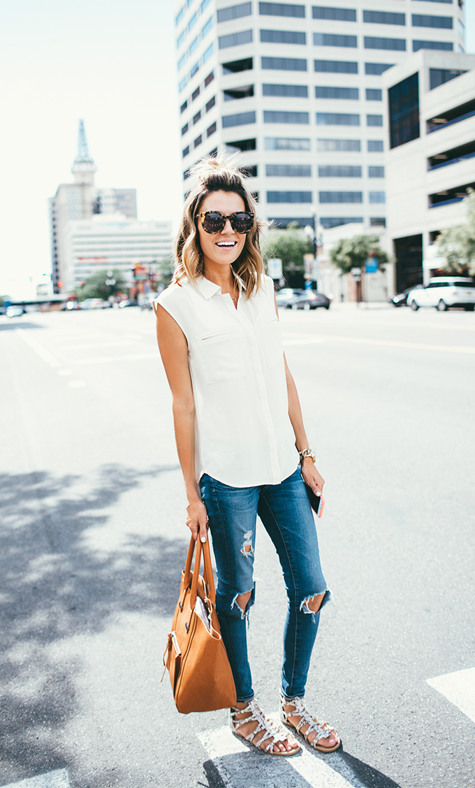Christine Andrew is looking fresh and stylish in this simple combination of a white sleeveless blouse and ripped denim jeans. We suggest you wear this look with sandals and maybe a straw hat for those extra sunny days! Top/Jeans: Nordstrom.
