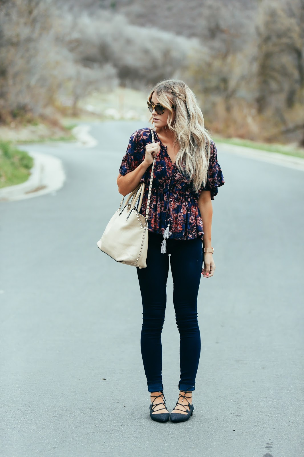 The floral trend is a natural choice for a cute spring outfit! Cara Loren is wearing a beautiful floral printed blouse with jeans and strappy flat sandals to create an easygoing summer vibe. Top/Jeans: Shopbop, Shoes: DSW.