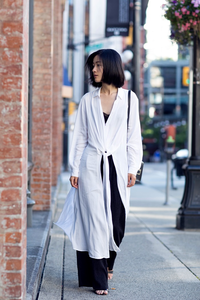 Claire Liu looks edgy and alternative in this gorgeous long white shirt, worn over an intricately detailed lace bralette and paired with flared black trousers. This monochrome style just oozes authenticity! Shirt/Trousers: H&M, Heels: Zara, Bag: Sophie Hulme.